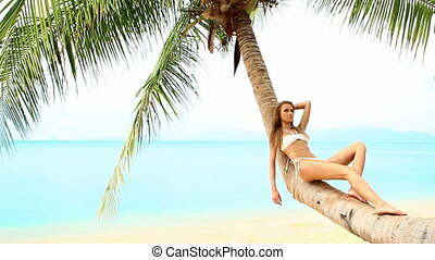 Relaxed woman resting on palm tree