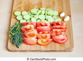 Cutted tomatoes and cucumbers with greens on a chopping...