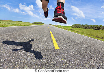 the legs and shoes of runner in action on the road