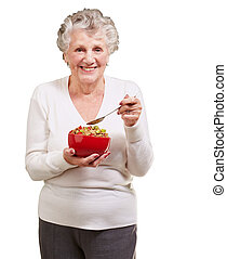 portrait of senior woman holding a cereals bowl against a...