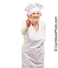 portrait of cook senior woman doing approval gesture over white background