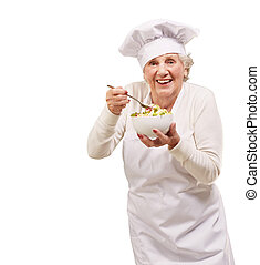 portrait of senior cook woman eating salad over white