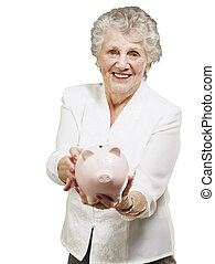 portrait of senior woman showing a piggy bank over white...