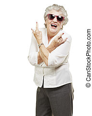 portrait of senior woman doing rock symbol over white background