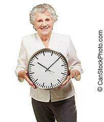 portrait of a happy senior woman holding clock over white