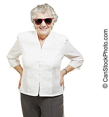 portrait of senior woman standing wearing sunglasses over...