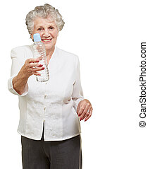 portrait of healthy senior woman holding a water bottle over...