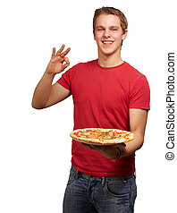 portrait of young man holding pizza and doing good gesture over white background