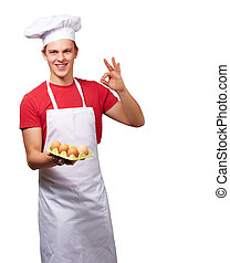 portrait of young cook man holding egg box and doing good gesture over white background