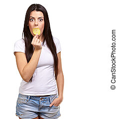 portrait of young woman holding potato chip on her mouth...