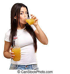 portrait of young girl drinking orange juice against a white background