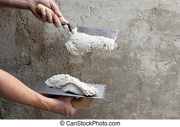 construction notched trowel and worker hands with white...