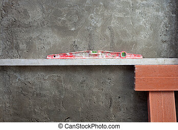 bubble spirit level tool in red on costruction cement