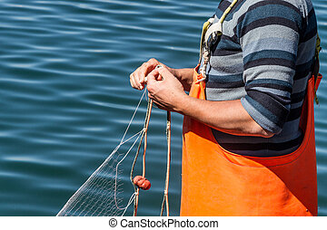fisherman sewing nets - A fisherman sewing nets