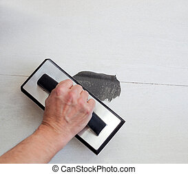 grouting tiles with rubber trowel man hand - grouting tiles...