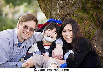 Disabled boy in wheelcahir surrounded by father and sister -...