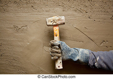 hammer man with gloves in grunge cement background - hammer...