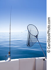boat fishing rod and landing net in sea - boat fishing rod...