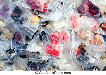 buttons for fashion clothes in plastic blister in messy...