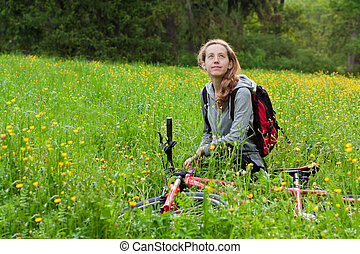 Happy woman cyclist with bike among the blooming nature