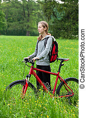 Woman cyclist with bike and backpack among the green nature