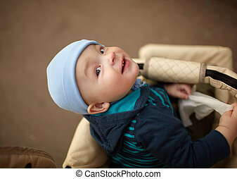 Kid in the buggy - Portrait of the little boy sitting in the...