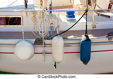 fender buoys on sailboat side with ropes