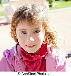 Blond little girl blue eyes portrait in pink
