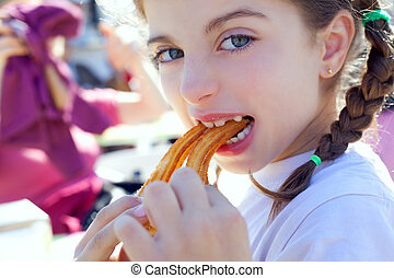 Blue eyes little girl eating churros smiling - Blue eyes...