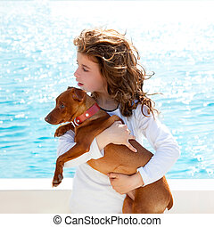brunette kid girl with dog on the sea view from a boat