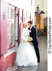 beautiful groom and the bride on the street of old town -...