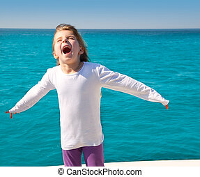 excited kid girl sailing in a boat open arms at the sea