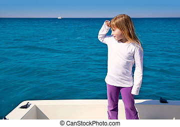 blond little kid girl sailing in a boat looking away