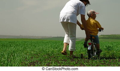 teaching child to ride a bicycle - Mother teaching child to...