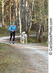 The sports woman with a dog run in park