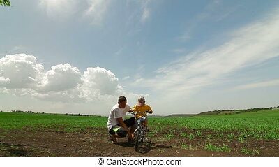 Happy Family Riding Bicycle. Father Helping Child Learn To...