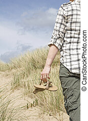 woman walking in sand dunes holding sandals