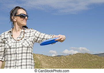 woman throwing frisbee in sand dunes