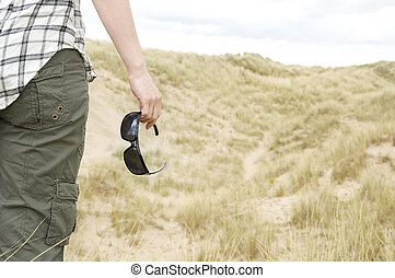woman with sun glasses in sand dunes landscape