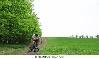 Child Learn To Ride A Bike - Father helping child learn to...