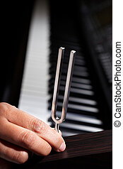 Piano and tuning fork - Hand holding tuning fork on top of...