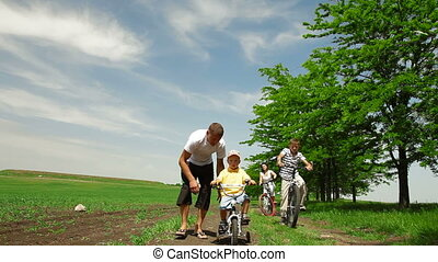 Family Riding Bicycles - A family bike ride down a country...