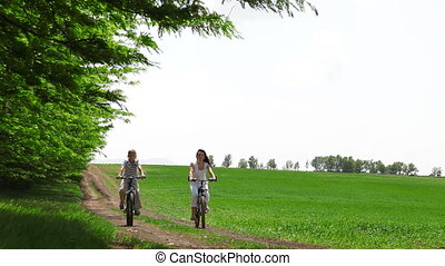 Family On Bikes - mother and child riding on a bicycle in a...