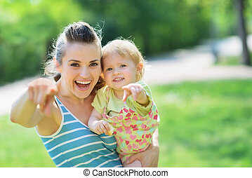 Happy mother and baby pointing in camera