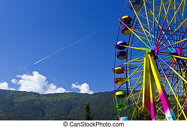 ferris wheel in the background of mountains