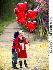 valentines kids with gift of balloons and kiss