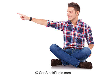 seated man pointing to his side - young casual happy man...