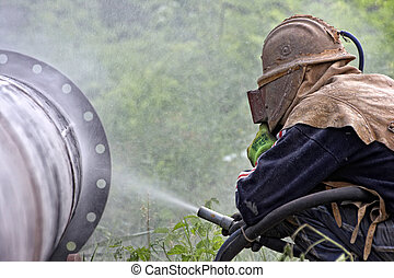 sandblasting - A worker sandblasting the weld during the...