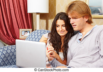 Happy couple spending with laptop - Happy couple spending...