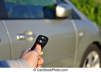 A hand holding car keys and a remote control for keyless...